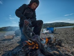 Tony Alexie is cleaning a freshly killed Canadian Goose on the banks of the Peel River © Peter Mather -